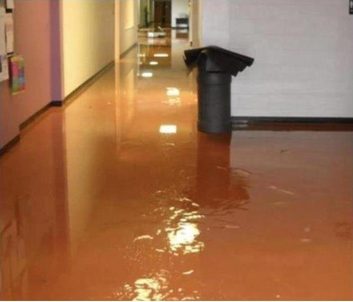 commercial tile hallway with water standing and a trash can